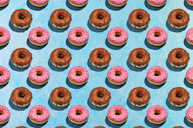 青の背景にピンクと茶色の釉薬とドーナツのシームレスなパターン。