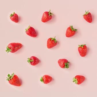 淡いピンクのテーブルに新鮮な美しさのイチゴのシームレスなパターン