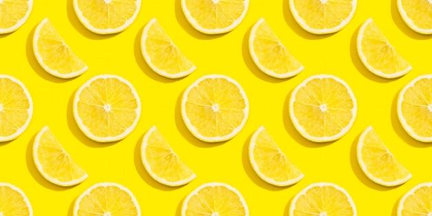Бесшовный фон из ломтиков лимона на желтом фоне.