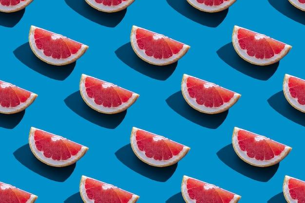 Бесшовный фон из оранжевого грейпфрута с тенью на синем фоне. минимальная модная концепция летних каникул. здоровый образ жизни в еде.