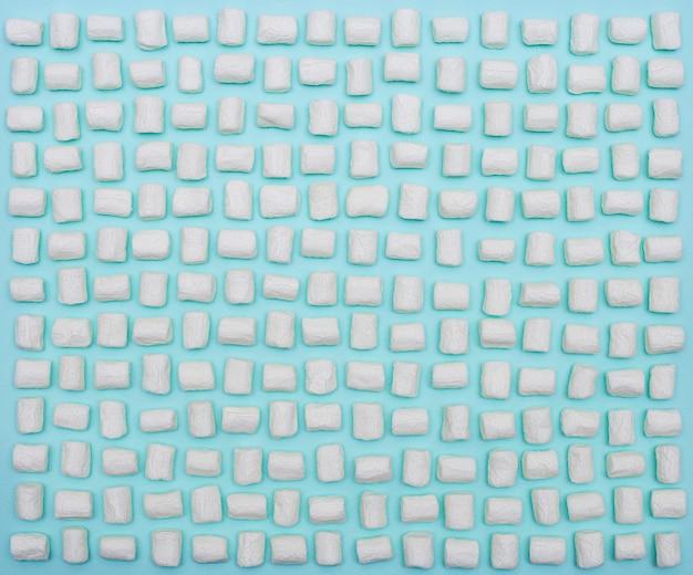 青い紙に白いマシュマロのシームレスなパターン