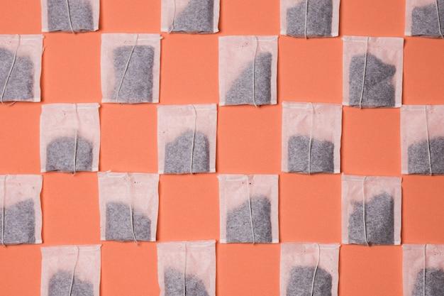色付きの背景上のティーバッグのシームレスパターン