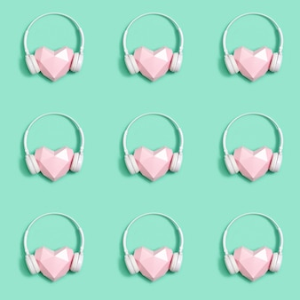 Seamless pattern of pink paper hearts in white headphones