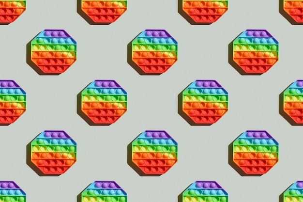 Seamless pattern of popular silicone colorful antistress pop it toy for child on gray background.