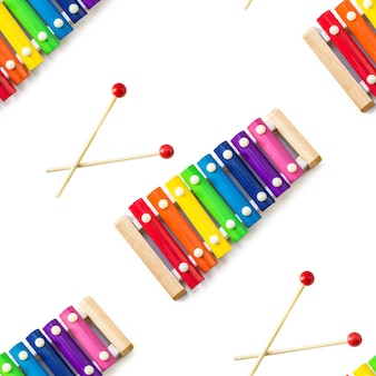 Seamless pattern of rainbow colored wooden toy 8 tone xylophone glockenspiel isolated on white back