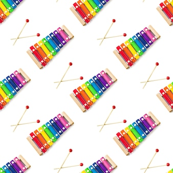 Seamless pattern of rainbow colored wooden toy 8 tone xylophone glockenspiel isolated on white backg