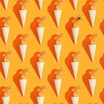 シームレスなパターン。アイスクリームコーンの小さなカボチャとクモ。テーマハロウィン、秋
