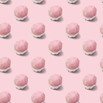 Seamless pattern of two-tone white and pink marshmallows on a pink surface