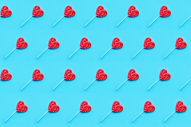 シームレスパターン。バレンタインデーbckground。青い背景のロリポップキャンディーハート。上面図。