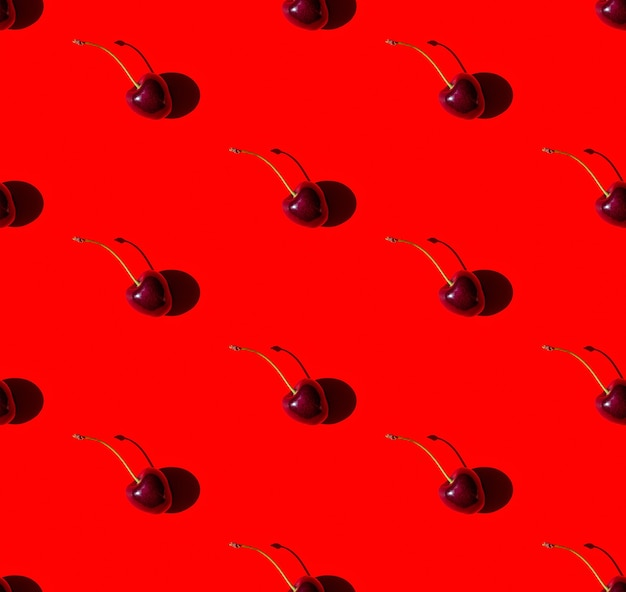 Seamless pattern with cherry berries on red background in sun light