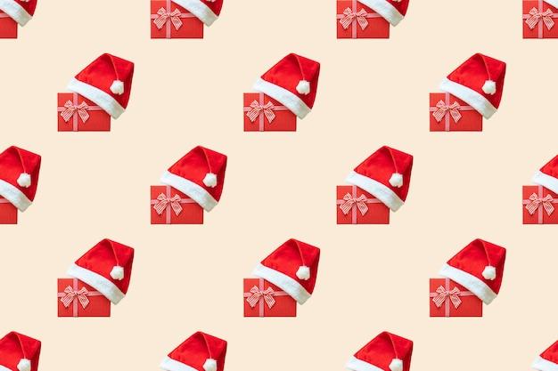 赤い贈り物の上に身に着けているクリスマスサンタの帽子とのシームレスなパターン