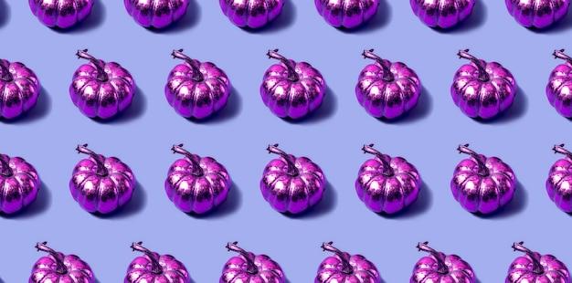 紫の背景に金色のピンクのカボチャとのシームレスなパターン。モダンなスタイルの秋のコンセプト。高品質の写真