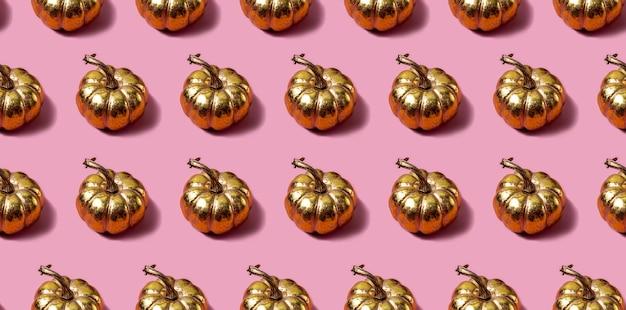 ピンクの背景に金色のカボチャとのシームレスなパターン。モダンなスタイルの秋のコンセプト。高品質の写真