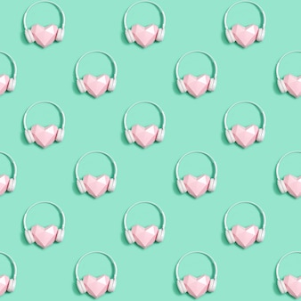 Seamless pattern with paper pink heart in white headphones, concept for music festivals, radio stations, music lovers