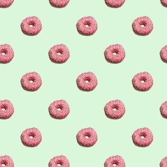 파스텔 녹색 배경에 분홍색 글레이즈드 도넛이 있는 매끄러운 패턴입니다. 음식 달콤한 패턴입니다.