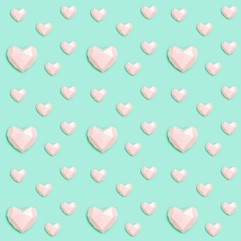 민트 색 종이에 분홍색 다각형 종이 심장 모양으로 완벽 한 패턴입니다. 사랑 개념.