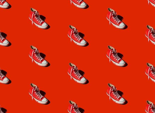 Бесшовный фон с кроссовками на красном фоне