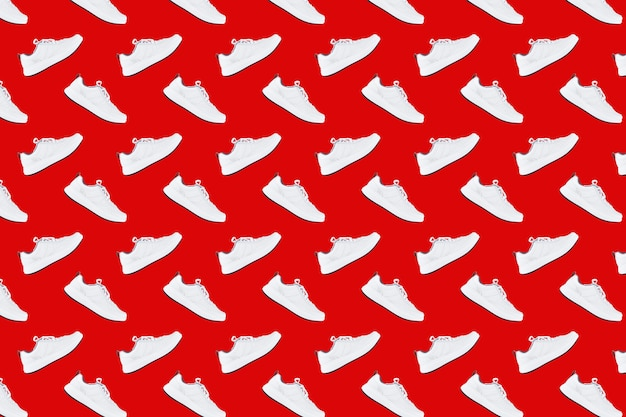 Seamless pattern with white sneakers on red background