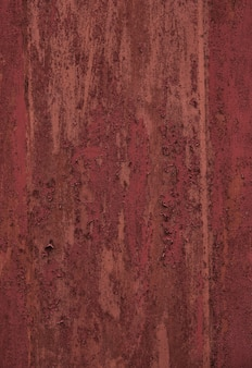 時代によって風化した古い塗装された金属製のドアのシームレスな赤いパチパチテクスチャ。