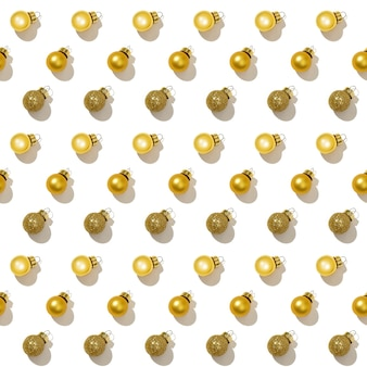 Бесшовные регулярный творческий узор с яркими блестящими маленькими золотыми елочными шарами