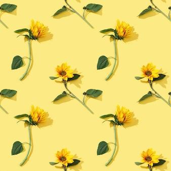 黄色い紙に美しいひまわりからシームレスな規則的なパターン。
