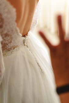 Seamstress buttoning the pretty wedding dress, elegant and bare back.