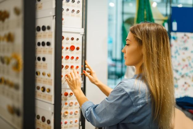 Швея покупает пуговицы в текстильном магазине. женщина, выбирающая инструменты для шитья, портной в магазине, портниха