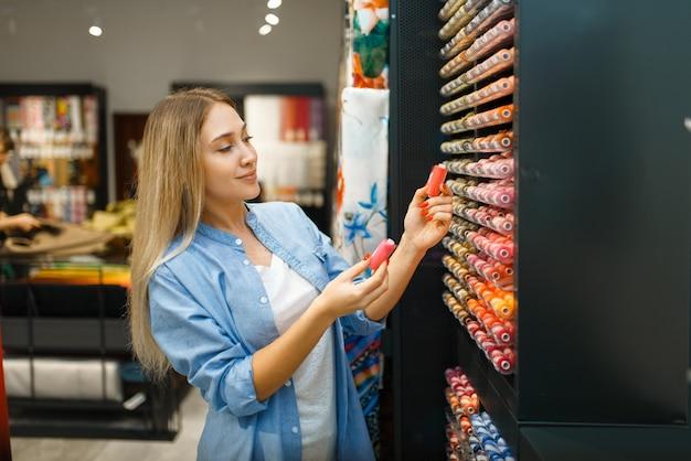 Швея покупает нитки в текстильной мастерской. женщина, выбирающая инструменты для шитья, портной в магазине, портниха