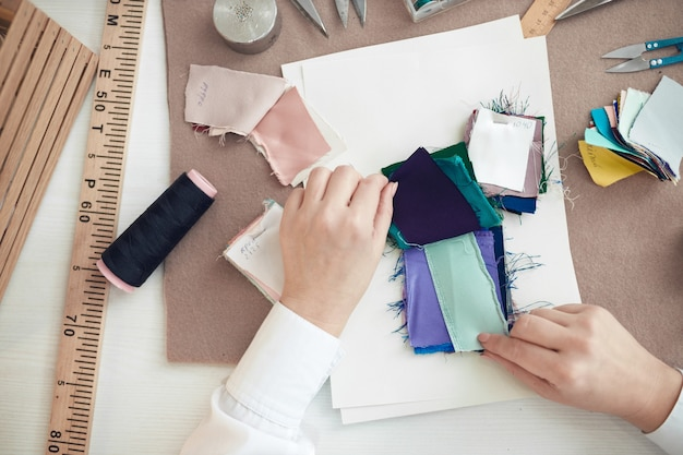 The seamstress chooses a sample of fabric for sewing clothes
