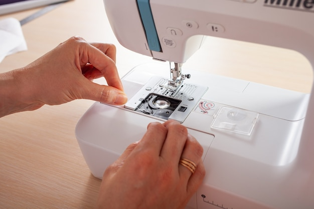The seamstress craftsman fills the thread into the bottom spool of the automatic sewing machine