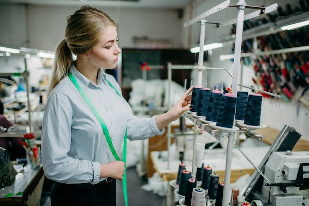 仕立て屋は、オーバーロックマシン、縫製材料に黒い糸を作成します。縫製工場での仕立てや洋裁