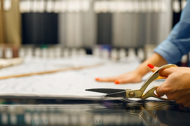 Швея режет ткань ножницами в текстильном магазине. женщина работает с тканью для шитья, портной в мастерской