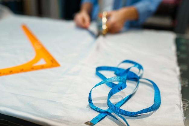 Швея режет ткань ножницами в текстильной мастерской. женщина работает с тканью для шитья, портной на рабочем месте