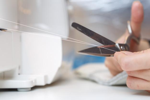 Seamstress cuts with scissors thread in sewing machine