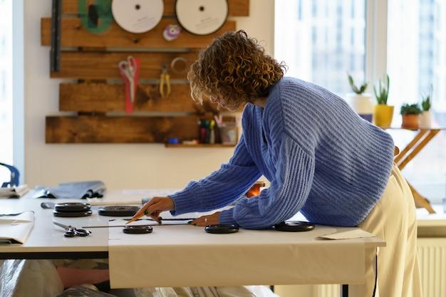 재봉사 초안 종이 패턴을 직물에 분필과 눈금자 옷 디자이너가 스튜디오에서 작업합니다.