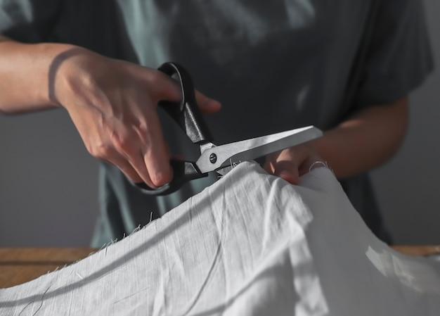 Руки швеи режут ткань швейными ножницами процесс работы портнихи крупным планом