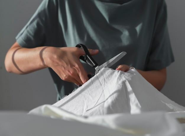 Швея вручает резку хлопчатобумажной ткани швейными ножницами крупным планом