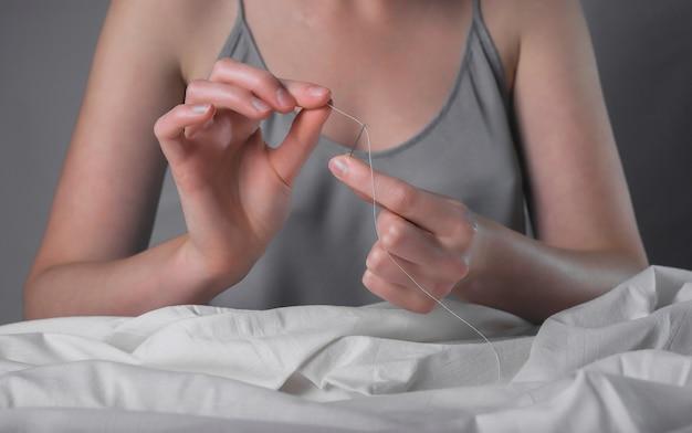 Руки швеи заправляют нить в игольное отверстие для ручного шитья