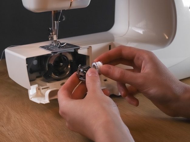 Seamstress hands inserting thread into spool or bobbin of sewing machine, starting work, fixing and repairing.