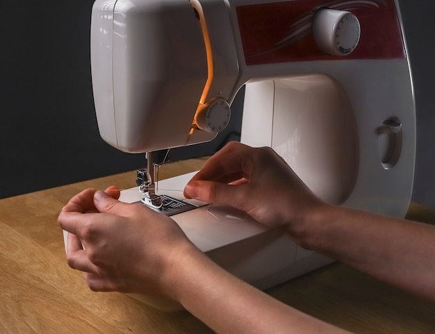 Seamstress hands inserting thread through needle hole in sewing machine starting work