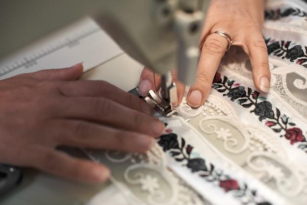 Руки швеи шить на современной машине