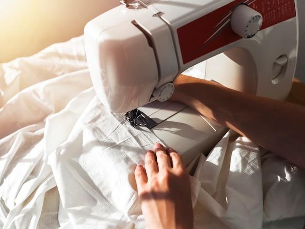 Руки швеи с хлопчатобумажной тканью работают в процессе работы швейной машины с текстилем