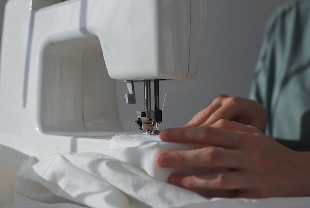 Руки швеи с льняной тканью в процессе работы швейной машины с натуральным хлопчатобумажным текстилем