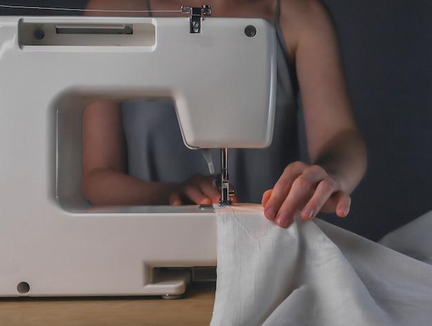 Руки швеи с льняной тканью на швейной машине, рабочий процесс с органическим натуральным хлопчатобумажным текстилем.