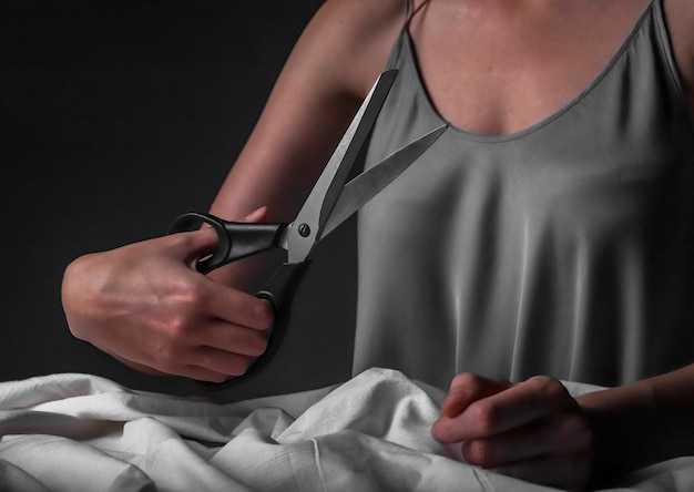 Seamstress hands with professional tailor sewing scissors closeup over cotton material