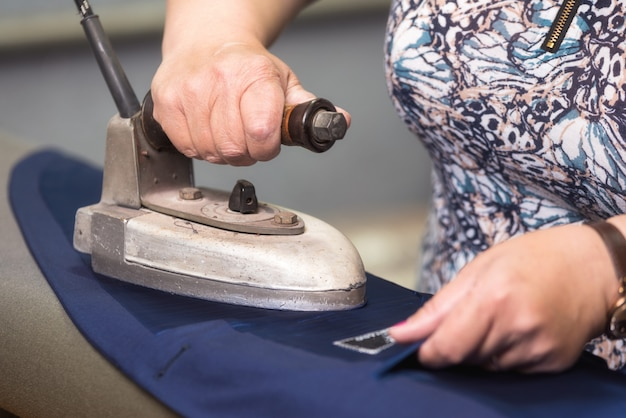 Seamstress ironing suit in tailor shop.