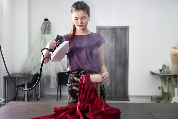Платье швеи утюги в швейной мастерской