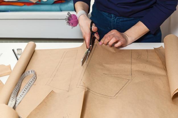 Швея вырезает рисунок к платью ножницами. разработка стиля и дизайна и создание одежды, услуги по пошиву и ремонту одежды, концепция швеи за работой