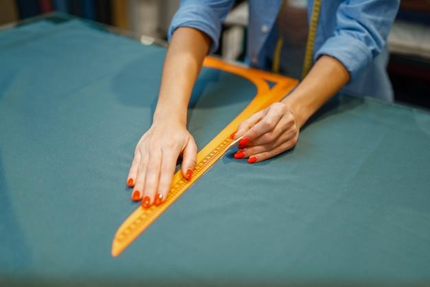 Швея измеряет ткань в текстильной мастерской. женщина работает с тканью для шитья, портной на рабочем месте, портниха