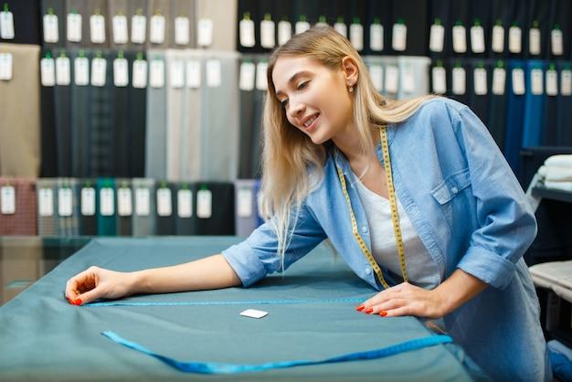 Швея измеряет тканевый материал в текстильной мастерской. женщина работает с тканью для шитья, портной на рабочем месте, портниха